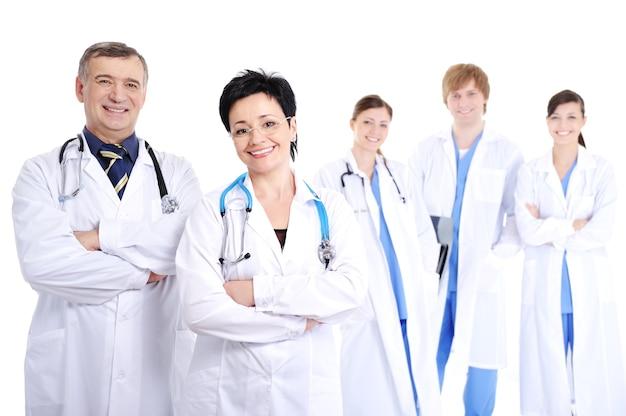 Grupo de cinco médicos alegres e sorridentes e felizes em batas de hospital