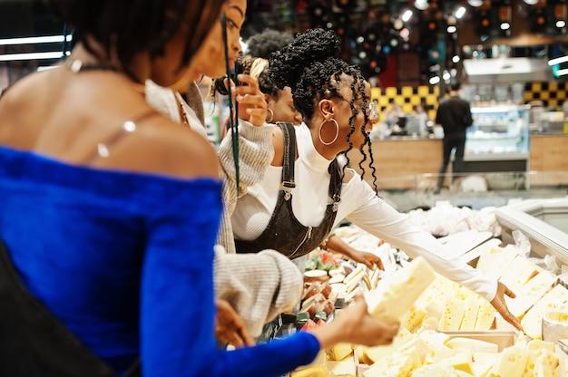 Grupo de cinco mulheres com carrinhos de compras escolher queijo no supermercado