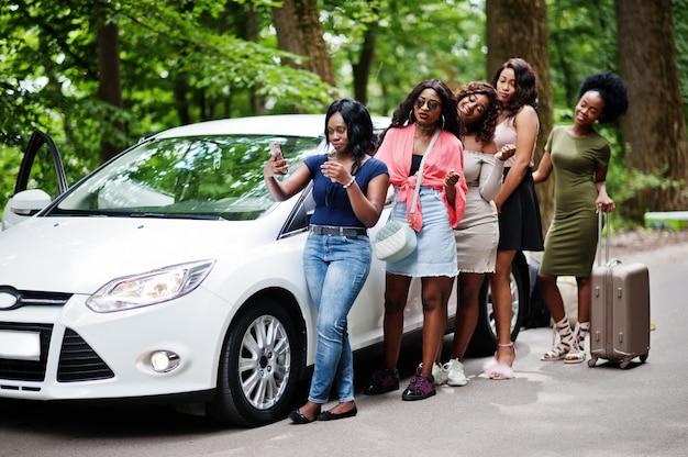Grupo de cinco mulheres felizes viajante posou contra carro com saco de terno