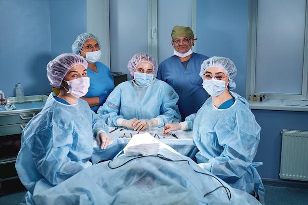 Grupo de cirurgiões profissionais médicos sobre a clínica na sala de operação