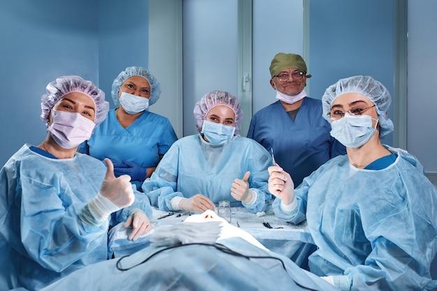 Grupo de cirurgiões profissionais médicos sobre a clínica