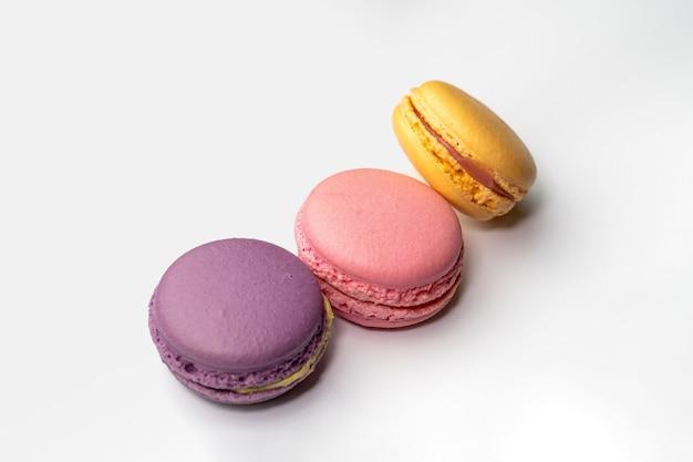 Grupo de close-up de 3 macarons em fundo branco, macaron de cor pastel, roxo, rosa e amarelo, mirtilo, morango e laranja