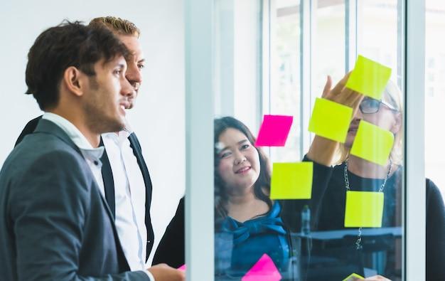 Grupo, de, colega negócio, pessoas, reunião, discutir, idéia, de, trabalho, em, notas pegajosas, ligado, parede vidro, em, escritório