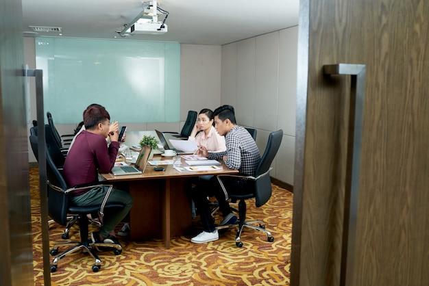 Grupo de colegas casualmente vestidos, sentado no escritório atrás de porta aberta e falando