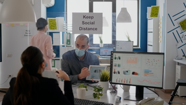 Grupo de colegas de trabalho com máscaras, analisando gráficos usando tablet digital, sentado no novo local de trabalho normal. colega que trabalha em segundo plano mantém o distanciamento social