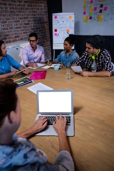 Grupo de colegas de trabalho durante a reunião e laptop