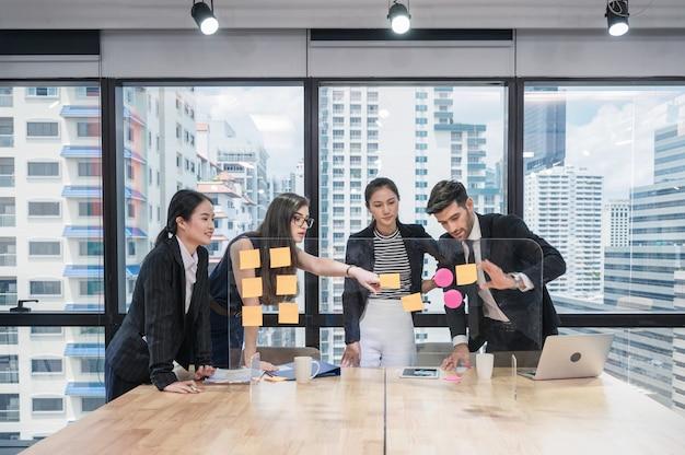 Grupo de colegas de trabalho multiétnicos analisando e discutindo ideias de negócios