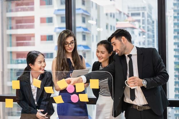 Grupo de colegas de trabalho multiétnicos, analisando e discutindo sobre a ideia de negócio com uma nota adesiva a bordo em um escritório moderno