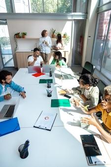 Grupo de colegas de trabalho multirraciais tem uma pausa para o almoço no escritório. imagem vertical. conceito de negócios.