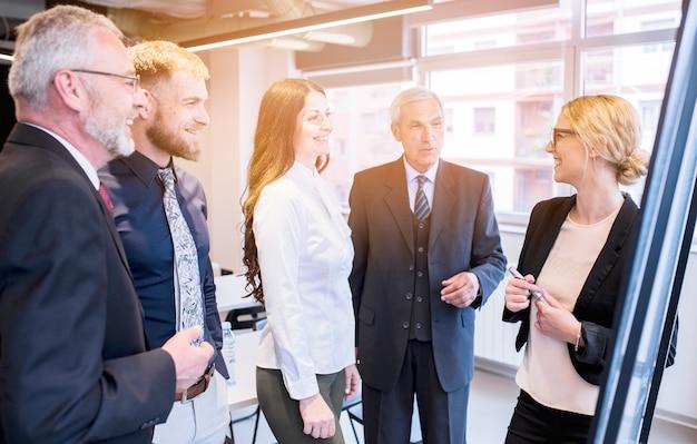 Grupo de colegas de trabalho olhando jovem empresária dando apresentação
