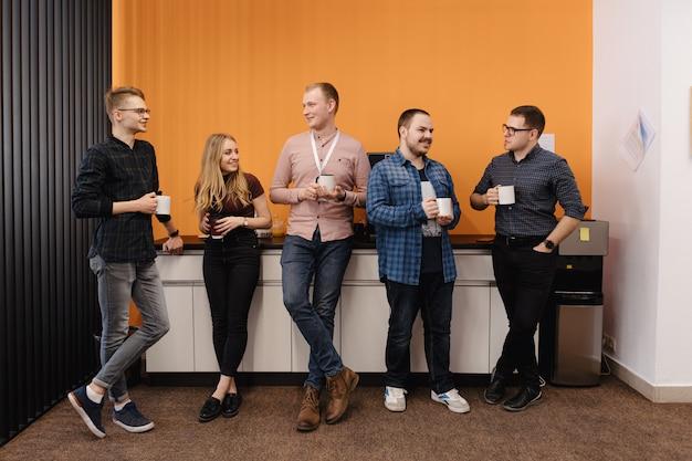 Grupo de colegas de trabalho tendo uma pausa para café