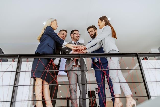 Grupo de colegas dedicados em pé em seu local de trabalho e empilhando as mãos. conceito de trabalho em equipe.