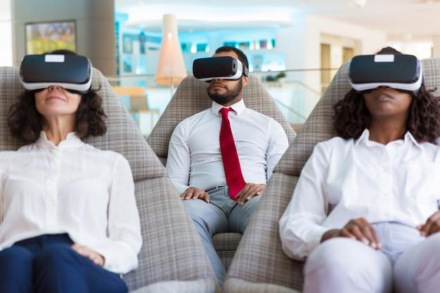 Grupo de colegas em fones de ouvido vr assistindo apresentação virtual