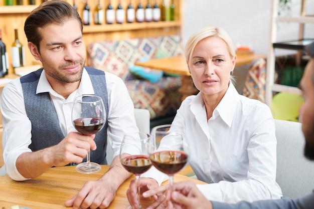 Grupo de colegas em trajes formais discutindo qualidade e outras características do vinho tinto em taças de vinho durante o trabalho