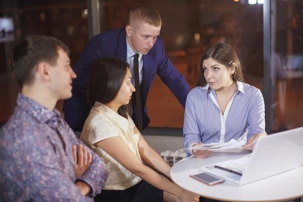 Grupo de colegas, gerentes de escritório à mesa com um laptop em um escritório noturno, discutindo gráficos em folhas de papel