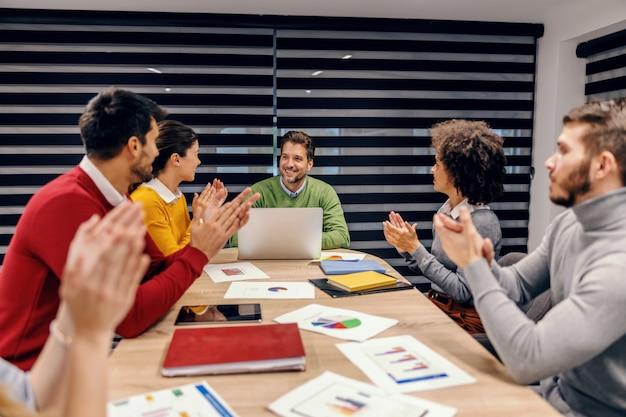 Grupo de colegas multiculturais batendo palmas para seu colega de trabalho. a empresa atingiu a meta mensal de dinheiro.