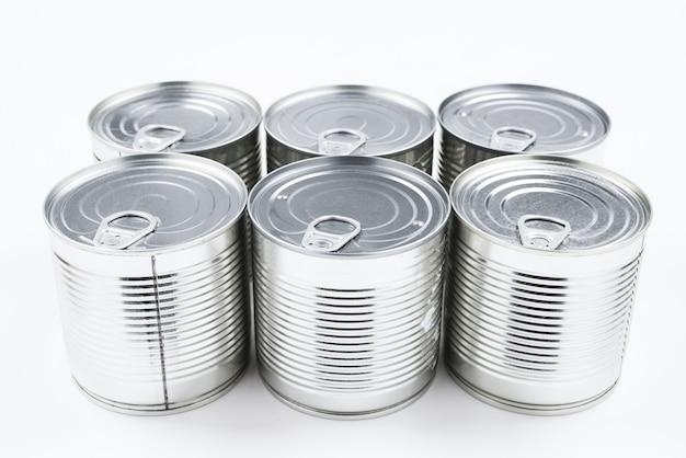Grupo de comida enlatada de prata sobre fundo branco.