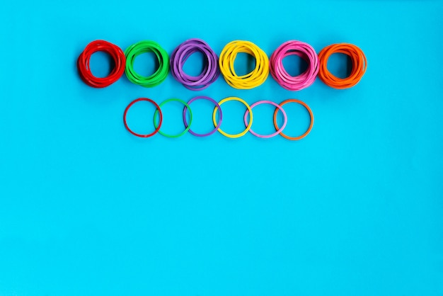 Grupo de conceito de trabalho em equipe de elástico colorido sobre fundo azul, com espaço de cópia