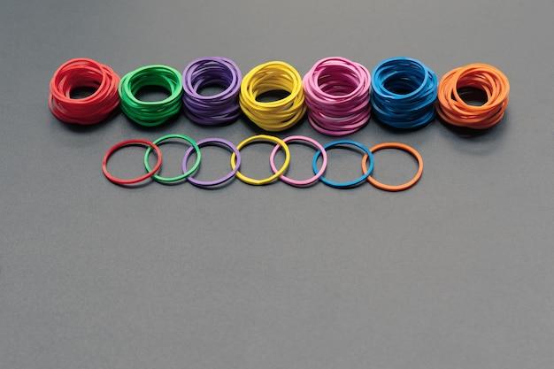Grupo de conceito de trabalho em equipe de elástico colorido sobre fundo preto, com espaço de cópia