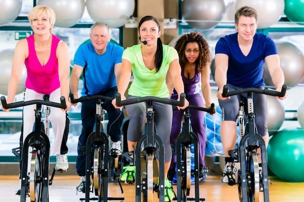 Grupo de condicionamento físico de homens e mulheres girando de bicicleta na academia para ganhar força e condicionamento físico