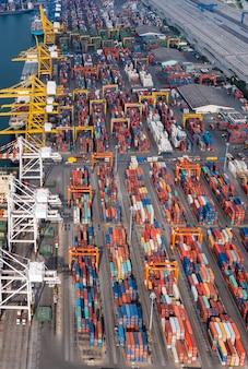 Grupo de contêineres de empilhamento de armazém em uma linha e guindastes descarregando carga no porto comercial de transporte