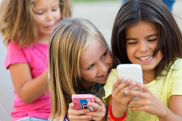 Grupo de conversas para crianças com telefones inteligentes no parque.