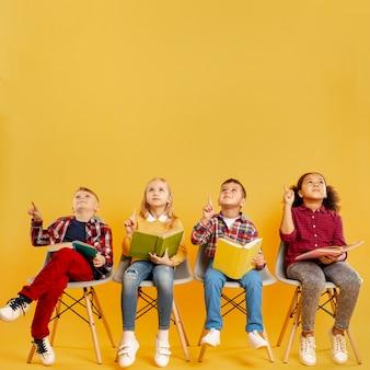 Grupo de cópia-espaço de crianças com livros apontando