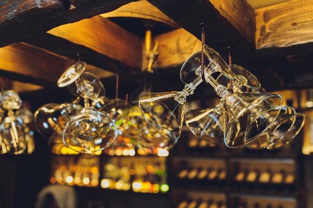 Grupo de copos de vinho vazios pendurados em vigas de metal em um bar.