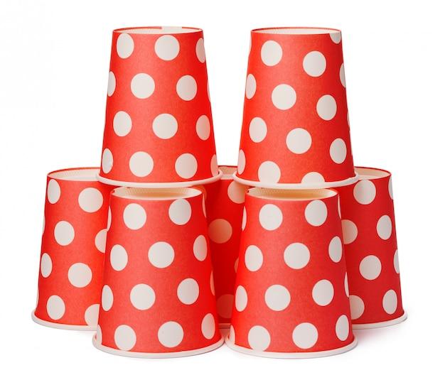 Grupo de copos pontilhados vermelhos descartáveis de papelão isolados