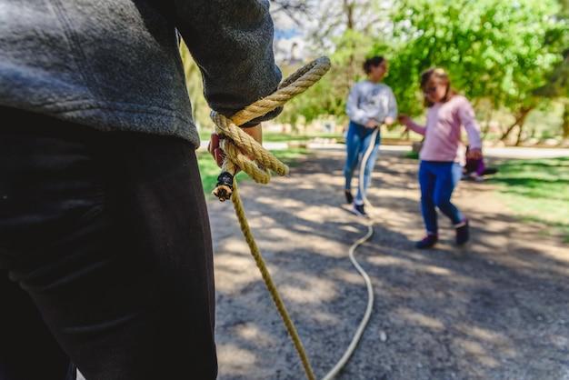 Grupo de corda de salto dos jovens em um parque em um dia ensolarado.