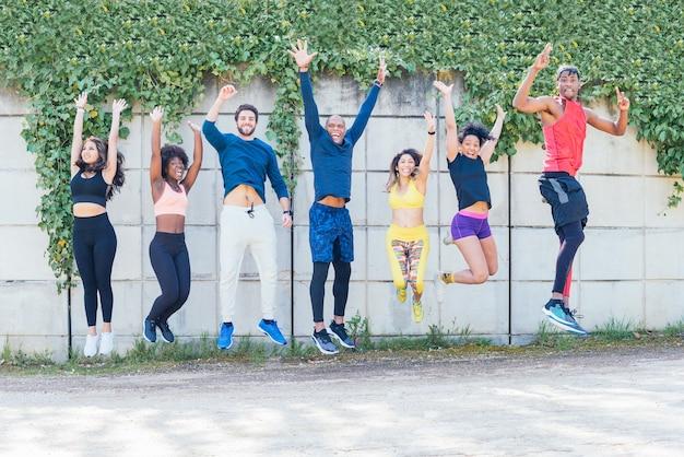 Grupo de corredores pulando ao mesmo tempo em um parque. enquadramento horizontal.