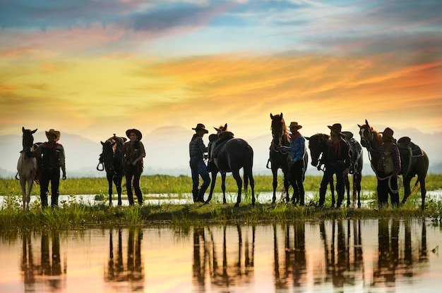 Grupo de cowboys segurando cavalos perto da água.