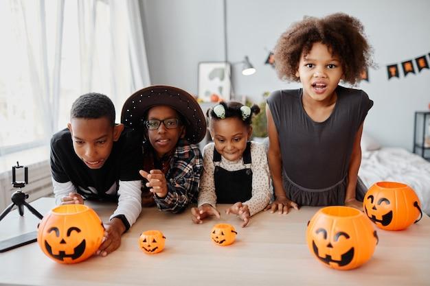 Grupo de crianças africanamerican vestidas com fantasias de halloween, posando com baldes de abóbora dentro de casa e ...