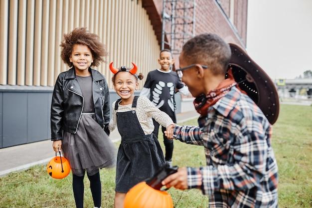 Grupo de crianças afro-americanas alegres, vestindo fantasias de halloween e correndo em direção à câmera enquanto t ...