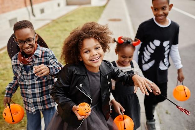 Grupo de crianças afro-americanas sorridentes, travessuras ou gostosuras ao ar livre e caminhando para a câmera segurando baldes