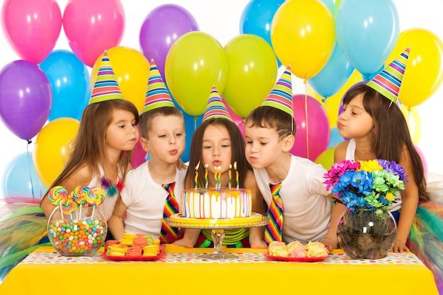 Grupo de crianças alegres comemorando a festa de aniversário e soprando velas no bolo conceito de férias