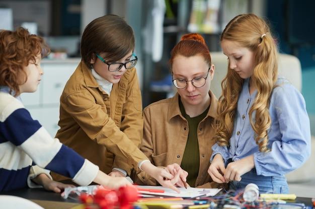 Grupo de crianças ao lado da professora enquanto constroem robôs durante a aula de engenharia na escola