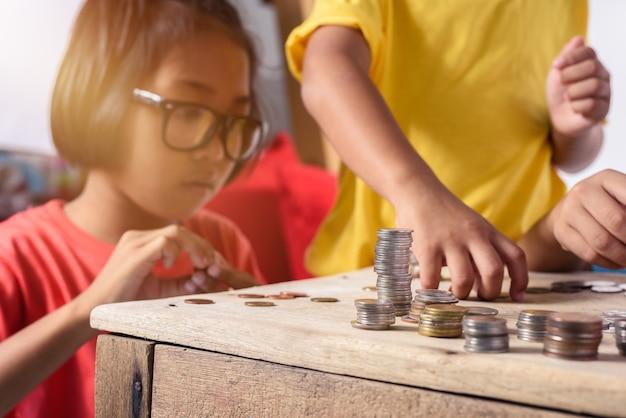 Grupo de crianças asiáticas estão ajudando a colocar moedas no cofrinho