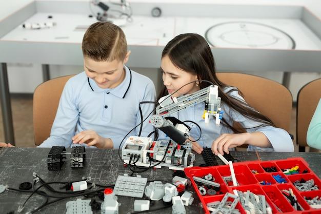 Grupo de crianças brinca com robôs montados com peças de plástico.