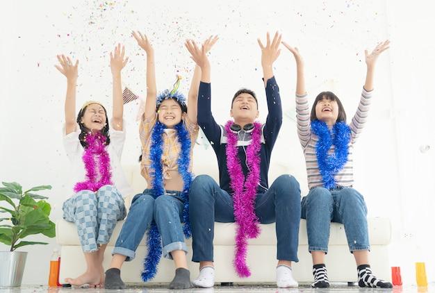 Grupo de crianças brincam com balões de ar, confetes na sala de luz na festa, conceito de infância feliz