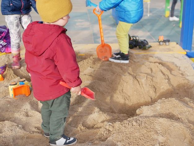 Grupo de crianças brincam na caixa de areia