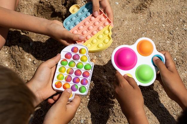 Grupo de crianças brincando com brinquedos da moda de verão estourando e fazendo uma covinha simples na praia