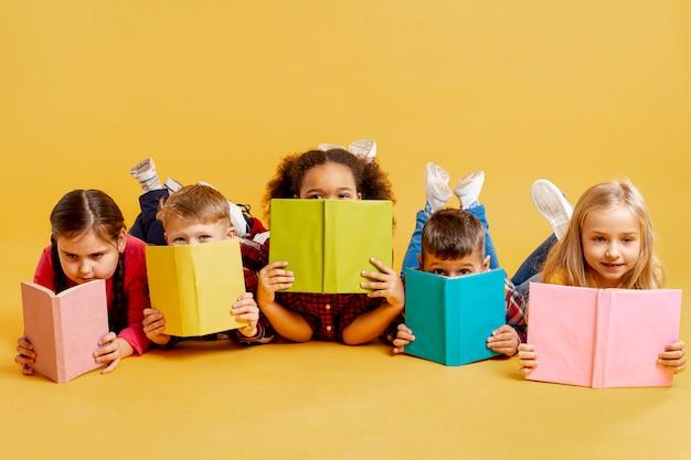 Grupo de crianças cobrindo o rosto com livros