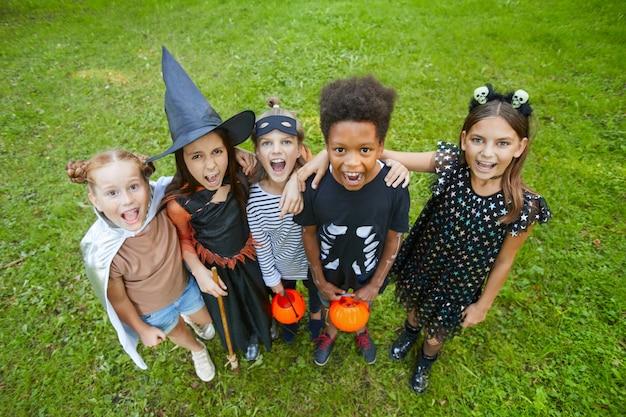 Grupo de crianças com fantasias de halloween gritando para a câmera em pé na grama verde ao ar livre