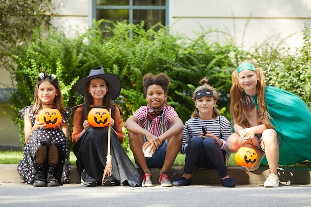 Grupo de crianças com fantasias de halloween sentadas no chão e na festa de halloween