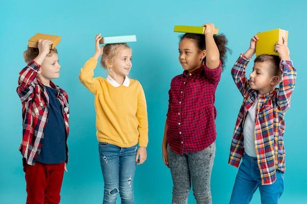Grupo de crianças com livros na cabeça