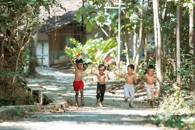 Grupo de crianças correndo sem roupa segurando bandeiras
