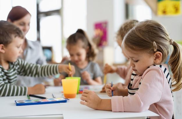 Grupo de crianças da creche com o professor dentro de casa na sala de aula, pintando.