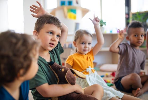 Grupo de crianças da creche, sentadas no chão dentro de casa na sala de aula, levantando as mãos.