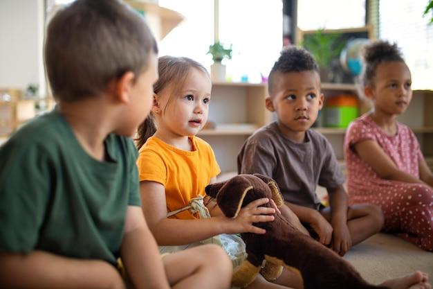 Grupo de crianças da creche, sentadas no chão dentro de casa na sala de aula, ouvindo o professor.